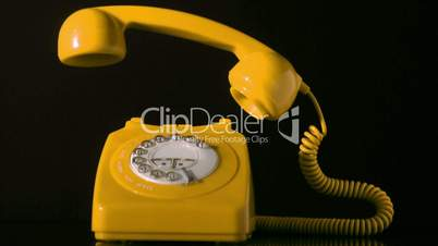 Receiver falling on yellow dial phone on black background