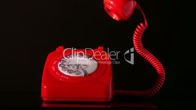 Receiver falling on red dial phone on black background