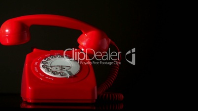 Receiver falling onto red dial phone on black background