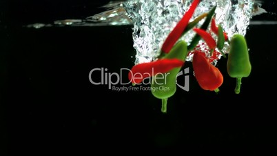 Red and green chili peppers falling into water