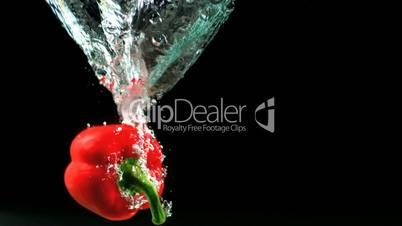 Red pepper falling into water and floating