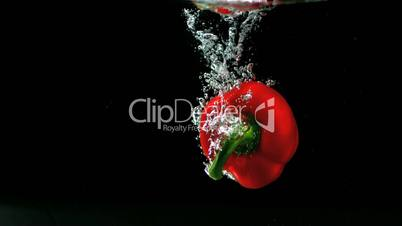 Red pepper falling in water and floating