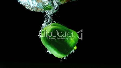 Green pepper falling in water and floating