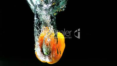 Yellow pepper falling in water and floating