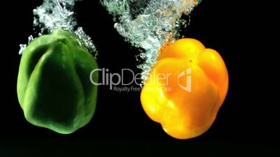 Yellow and green peppers falling in water and floating