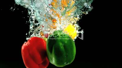 Three peppers falling in water and floating
