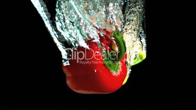 Yellow and red peppers falling into water and floating