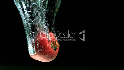 Apple falling into water and floating