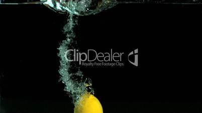 Lemon falling in water on black background
