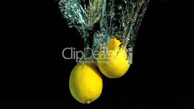 Two lemons dropping in water