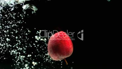 Red apple dropping into water and floating