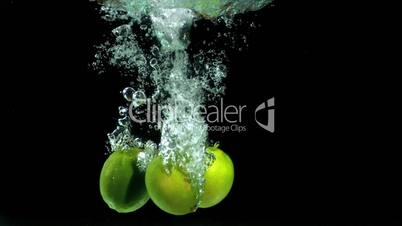 Three limes dropping into water
