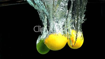 Lemons and limes dropping in water