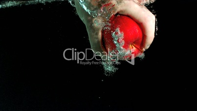 Hand taking apple from water