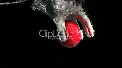 Hand taking an apple from water