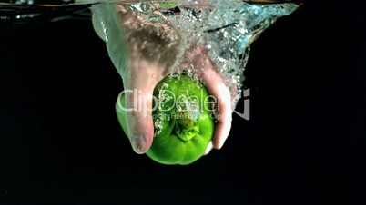 Hand taking green pepper from water