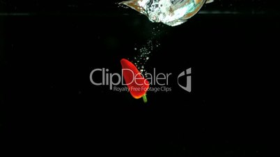 Red chili falling into water