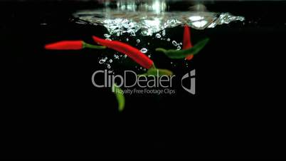 Red and green chilies falling into water