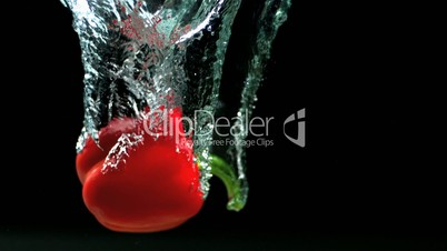 Red pepper falling in water