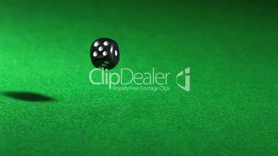 Black dice falling on green table and spinning