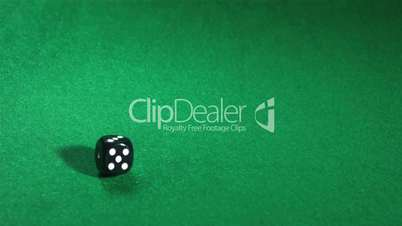 Black dice rolling over green table