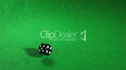 Black dice rolling on green table