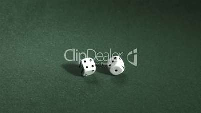 White dice rolling on green table