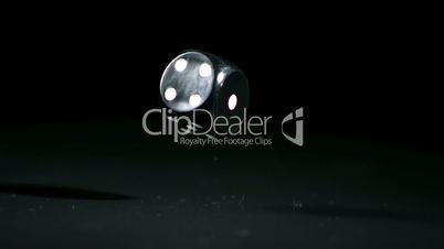 Black dice falling on black background