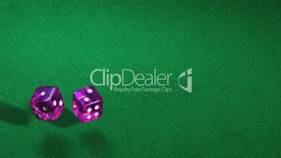 Purple dice rolling on green table
