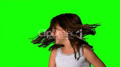 Little girl tossing her hair on green screen