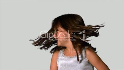 Little girl tossing her hair on white background