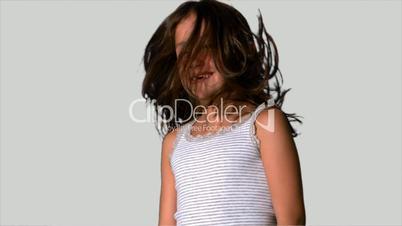 Little girl shaking her hair on white background