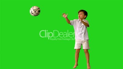 Happy little boy jumping and dropping rugby ball on green screen