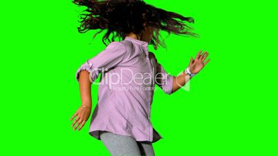 Girl jumping and spinning on green screen