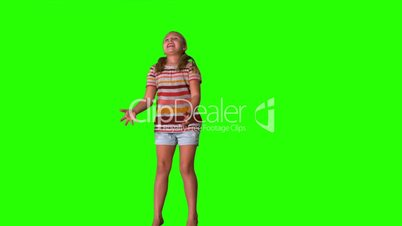 Girl jumping and catching teddy on green screen
