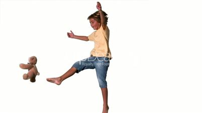 Boy jumping to kick teddy bear on white background