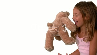 Cute little girl catching teddy bear on white background and jumping