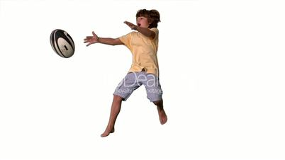 Young boy jumping up and catching a rugby ball on white background