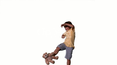 Little boy jumping up and kicking teddy on white background
