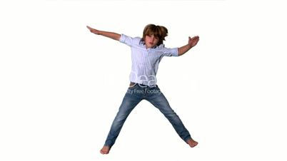 Little boy jumping up in shirt and jeans on white background