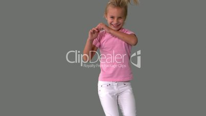Joyful little girl jumping on grey background