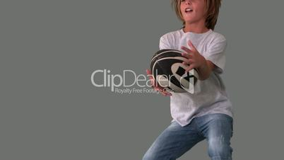 Boy jumping up to catch rugby ball on grey background close up