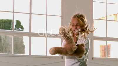 Happy girl with teddy bear jumping up and down in front of window
