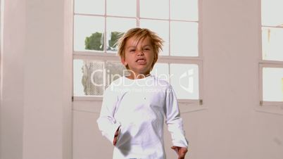 Boy in pajamas jumping and yelling in front of window