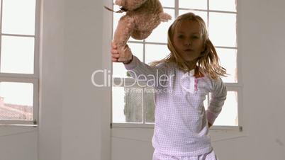 Girl in pajamas jumping and swinging teddy bear in front of window