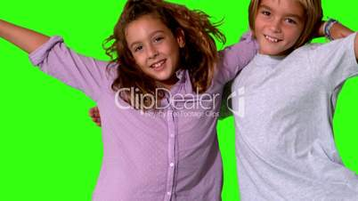 Brother and sister jumping into same shot and embracing on a green screen