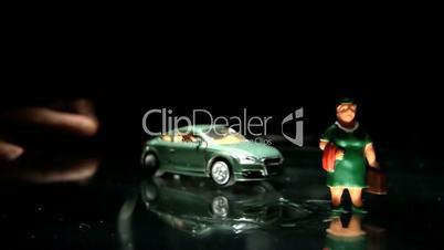 Green toy car hitting a woman figurine