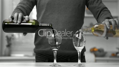 Man pouring red and white wine into two glasses