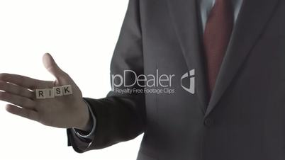 Man in suit dropping letter pieces spelling risk