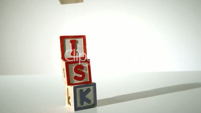 Risk spelled out in blocks falling over